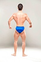 Bodybuilder flexing muscles, rear view