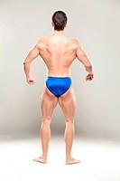 Bodybuilder flexing muscles, rear view