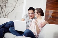 Young couple sitting on sofa with laptop