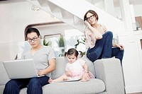 Parents sitting on sofa with laptop, daughter 2_3 playing with digital tablet