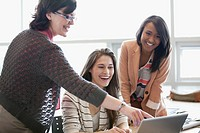 College teacher laughing with female students (thumbnail)