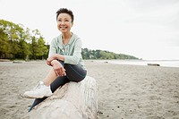Mature Asian woman relaxing at the beach (thumbnail)