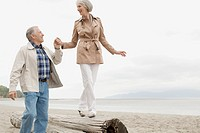 Man assisting woman walking on driftwood
