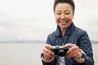 Mature Asian woman with camera