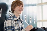 Male middle school student hanging by lockers
