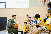 Teacher instructing students on basketball