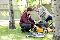 Father and son maintaining lawnmower (thumbnail)