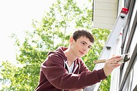 Teenage boy painting exterior of home