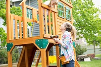 Mature woman drilling wooden play structure