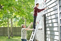 Father and son painting exterior of home