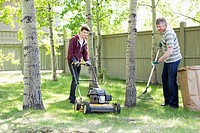 Teenage son and father doing yard work