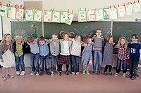 Group of schoolchildren 6_7 posing in front of blackboard