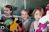 Group of schoolchildren 6_7 posing in front of blackboard with their toys