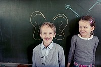 Schoolboy and girl 6_7 posing in front of blackboard with butterfly wings and feeler written on it