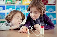 Two schoolgirls 6_7 experimenting with electricity in science class