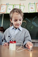 Young boy 6-7 experimenting with electricity in science class (thumbnail)