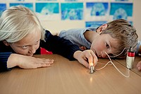 Young girls 6__7 and boys 6_7 experimenting with electricity in science class