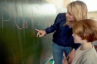 Female teacher and young school boy 6_7 standing by blackboard