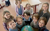 Group of school children 6_7 standing next to globe