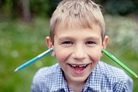 Young boy 8-9 posing with two pens stuck in his ears (thumbnail)