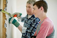 Father and teenage son doing home renovations