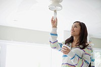 Mid adult latino woman replacing lightbulb.