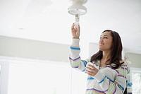 Mid adult latino woman replacing lightbulb.