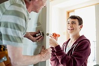 Father and teenage son replacing door lock