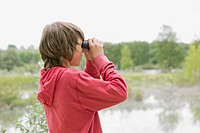 Middle school student using binoculars on a field trip