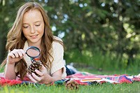 Student looking at pinecone through magnifying glass