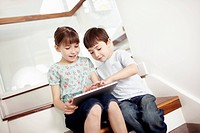 Brother 4_5 and sister 6_7 using digital tablet