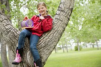 Female elementary student sitting in tree