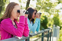 Female students with binoculars on a field trip