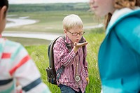 Elementary student blowing seeds during field trip