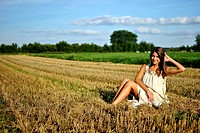 nice girl in national dress sitting on a field in rural areas