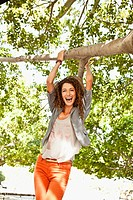 Young attractive woman hanging on tree branch