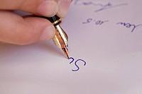 Kinderhand schreibt mit einem Füllfederhalter
