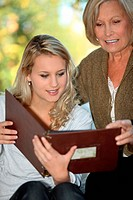 Young woman and her grandmother looking at a photo album