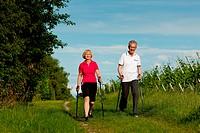 Glückliches älteres Paar beim Nordic Walking im Summer