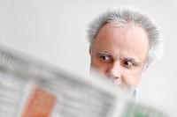 ein Mann liest erstaunt eine Zeitung
