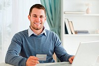 Smiling male with credit card at his laptop