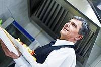 male chef presenting food meal in kitchen