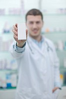 portrait of handsome young pharmacist chemist man standing in pharmacy drugstore