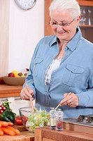 An old lady making a salad.