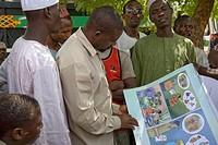 A man in Yankaba market Nassarawa area, Kano, Nigeria looks at a flipchart depicting how partner reduction reduces chances of HIV/AIDS transmission, T...