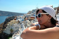 Beautiful young Greek woman in fashion clothes have fun at n the streets of Oia, Santorini, Greece
