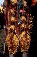 Detail of traditional female Khampa wearing gold & coral hair pieces at the Litang Horse Festival _ Sichuan Province, China