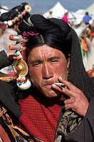 Khampa man with gold & coral hair peices smokes at the Litang Horse Festival _ Kham, Sichuan Province, China, Tibet