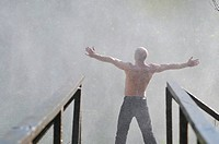 standing man with wide opened arms with waterfalls in background and representing freshness healthy lifestyle and success concept