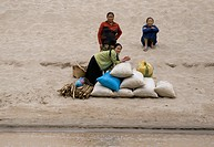 Laotian girls wait with a load of goods on the banks of the Mekong River above LUANG PROBANG _ LAOS
